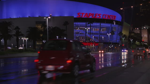 stockvideo's en b-roll-footage met pan right to left as an suv car drives past the staples center basketball arena or stadium in downtown los angeles. also used as a concert hall or venue. the car also passes the convention center. - los angeles convention center