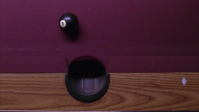 vídeos y material grabado en eventos de stock de close angle, birdseye pov of purple pool table in bar or tavern or pool hall. cue ball knocks eight ball into side pocket. billiards. - salón de billares