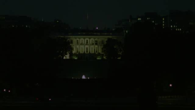 established wide angle of white house lit at night. front yard and trees surround white house. see lights on top of gate and some traffic in foreground. obscured buildings in background. - white house washington dc stock videos and b-roll footage