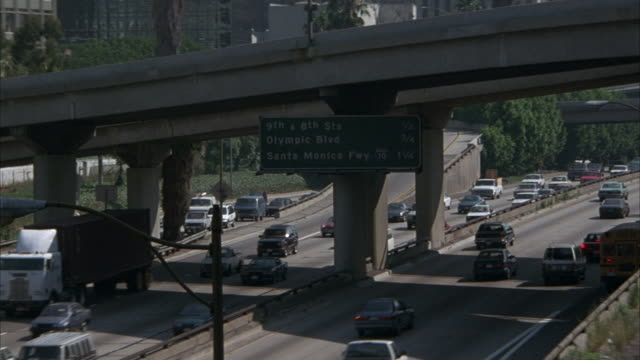 medium angle of traffic on 110 freeway. ramp above and across freeway. signs read 9th & 8th sts, olympic blvd, santa monica fwy - 10. - 1996 stock videos and b-roll footage