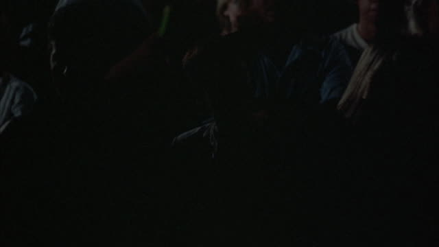 CLOSE UP. ROCK CONCERT. YOUNG AUDIENCE DRESSED IN EARLY 1980'S ATTIRE. CROWD CASTS DARK SHADOWS AS THEY WATCH CONCERT, SOME DANCE TO MUSIC, OTHERS CLAP THEIR HANDS.