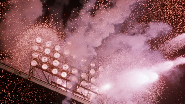 medium angle shot of exploding stadium lights. see sparks flying in all directions. multiple explosions. light fade off at end of clip. explosions. - exploding stock videos & royalty-free footage