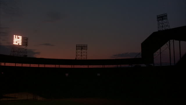 WIDE ANGLE OF BASEBALL STADIUM. LEFT LIGHTS TURN ON, THEN CENTER AND RIGHT LIGHTS. SKY LOOKS LIKE SUNSET.