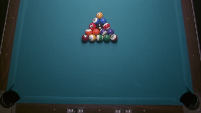 vídeos de stock e filmes b-roll de medium angle from above pool table looking straight down of half of the table. see balls racked in triangle formation. see cue ball enter from top of screen and break balls. do not see any of the balls go into the two corner pockets that are visible. - mesa de bilhar