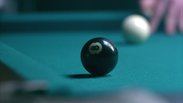close angle of corner pocket of pool table. see hand holding cue stick aim white ball. white ball hits 8-ball as  8-ball rolls into corner pocket. zooms in on corner pocket. white ball moves to right. - cue ball stock videos & royalty-free footage