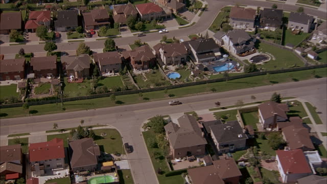 vidéos et rushes de aerial tracking shot of gray suv traveling through residential area with tract houses. - toronto