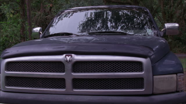 pan right to left of dodge ram pickup truck parked in woods, forest or park. jarring or shaking as if movement in truck bed. - pickup bildbanksvideor och videomaterial från bakom kulisserna
