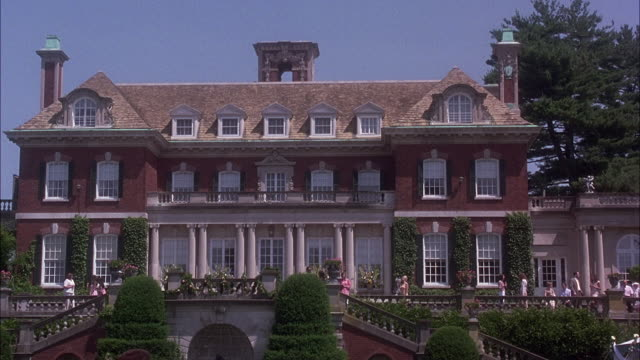 wide angle of mansion at old westbury gardens. house is upper class, three story, red brick, georgian-style. see people dressed up scattered around veranda, gardens. estates. - old westbury stock videos and b-roll footage