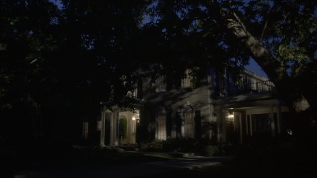 medium angle of side of two story upper class house partially blocked by trees in front yard. see porch light and lights inside house lit. - https stock videos & royalty-free footage