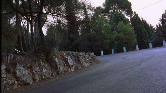 TRACKING SHOT OF CITROEN DS 21 CHASED BY 1985 BMW 520I SEDAN ON WINDING COUNTRY OR MOUNTAIN ROAD. CAR CHASES.