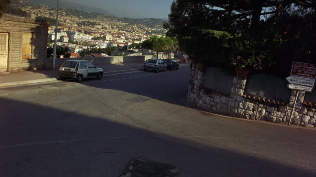 HIGH ANGLE DOWN OF SHARP RIGHT TURN OR SWITCHBACK ON WINDING ROAD OVERLOOKING URBAN AREA. PEUGEOT HATCHBACK AND PEUGEOT SEDAN APPROACH INTERSECTION AND STOP.  HILLSIDE. STREET SIGNS WITH FRENCH CITIES SUCH AS MONACO. EUROPE.