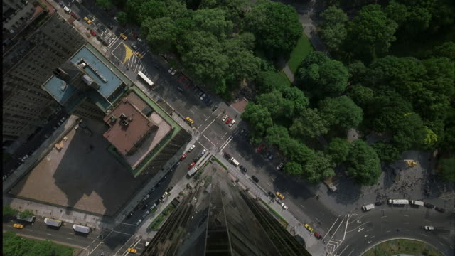 vídeos y material grabado en eventos de stock de aerial birdseye pov camera mounted on track. camera pulls forward over edge of high rise looking straight down at city street. camera falls down side of building then pans up to central park. - 2001