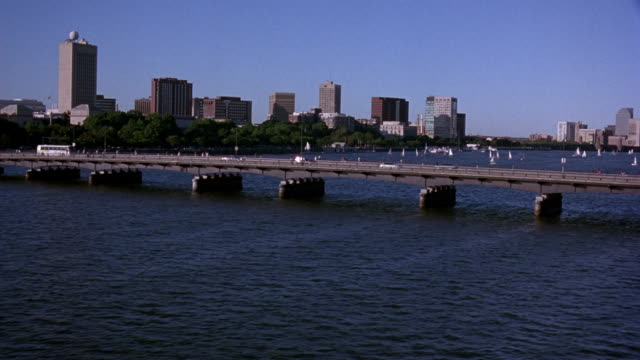 vidéos et rushes de aerial of boston skyline and charles river with bridge in center. moves forward and right to fly over residential area. - boston