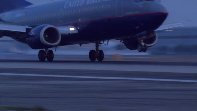 tracking shot of united airlines airplane landing on runway at airport. could be lax, burbank or santa monica airports. neg cut. view at end obscured by bush. - luftfahrzeug stock-videos und b-roll-filmmaterial