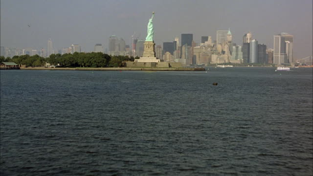 aerial over water, around statue of liberty and of new york city skyline. smoggy. - statue of liberty new york city stock videos & royalty-free footage