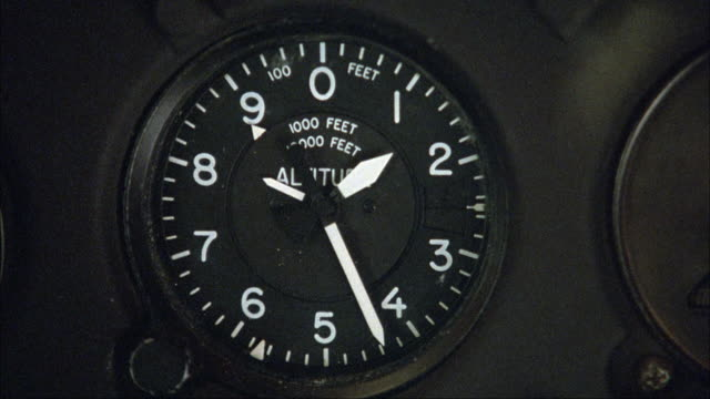 CLOSE ANGLE OF ALTIMETER ON INSTRUMENT PANEL IN AIRPLANE. ALTIMETER SLOWLY LOSES ALTITUDE. INSERTS.