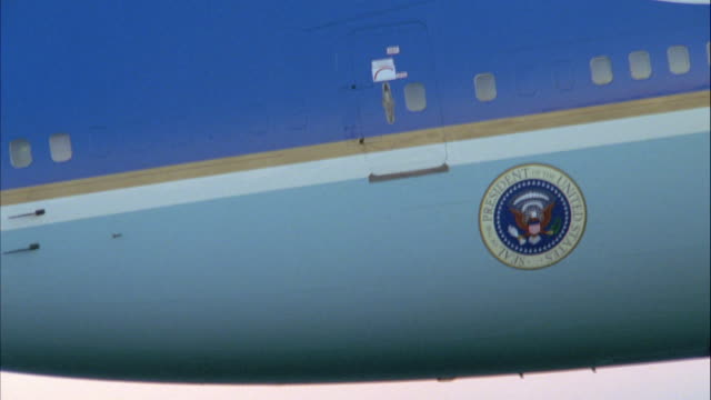 CLOSE ANGLE OF PRESIDENTIAL SEAL ON AIR FORCE ONE JET FLYING ACROSS SCREEN FROM RIGHT TO LEFT. AT END, CAMERA ZOOMS OUT TO SHOW MORE OF JET AND THEN ZOOMS BACK IN.