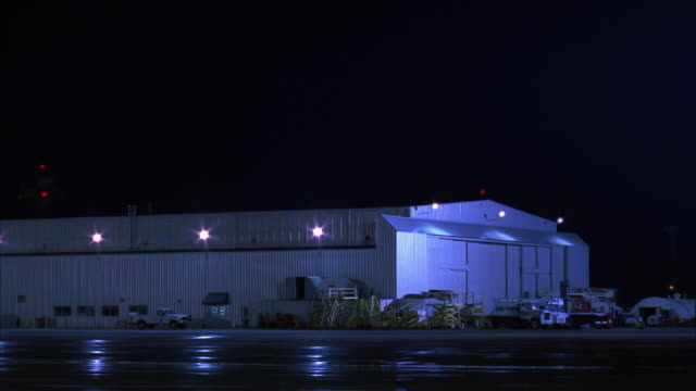 MEDIUM ANGLE OF AIRPORT HANGAR.  AIR FORCE ONE JET ENTERS SCREEN FROM RIGHT AND MOVES ACROSS TO LEFT.