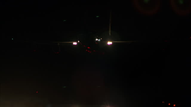 MEDIUM ANGLE TRACKING SHOT OF AIR FORCE ONE AIRPLANE, AIRPLANE DESCENDS AND LANDS ON RUNWAY TO LEFT. CLOSE UP OF AIRPLANE'S WHEELS. QUICKLY PANS RIGHT OF LIT RUNWAY.