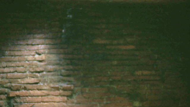 medium angle of brick wall. body and debris fall from above, falling through frame in a flurry of dust. neg cut. - ziegelmauer stock-videos und b-roll-filmmaterial