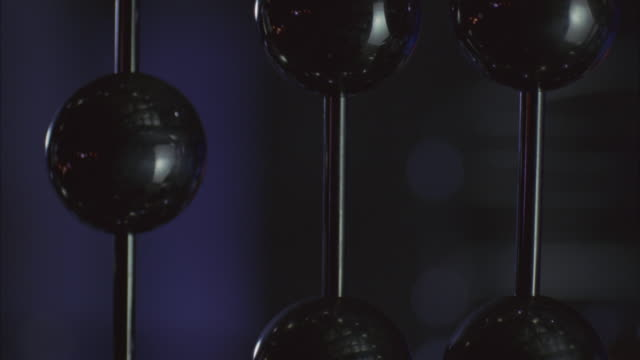 close angle of black balls or orbs that appear to be part of larger art piece or artwork or sculpture. rack focus reveals cage and granite column in background. - granite stock videos & royalty-free footage