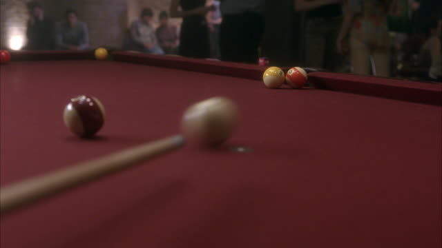 established close angle on cue stick hitting cue ball on pool table in nightclub. cue ball hits orange striped as well as red striped ball, but neither goes into side pocket. billiard. neg cut. - ビリヤード点の映像素材/bロール