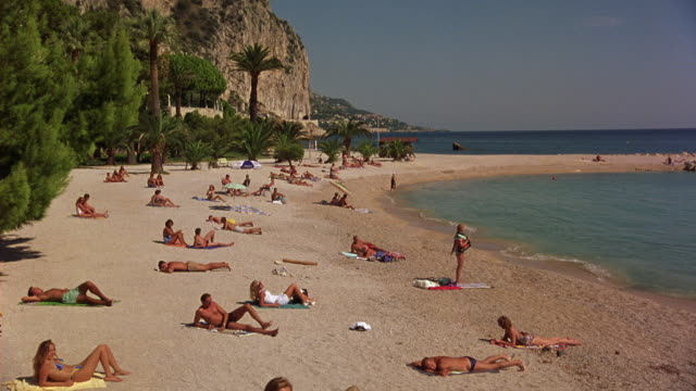 WIDE ANGLE OF SUNBATHERS WEARING BATHING SUITS ON TROPICAL BEACH IN MEDITERRANEAN EUROPE. PEOPLE STAND UP AND BEGIN RUNNING AWAY.