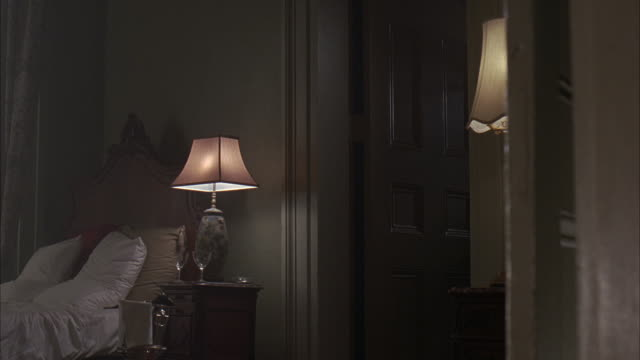 medium angle of home interior, could be a bed room or hotel.  ornate molding on the door frame, a carved wood headboard for the bed.  two crystal glasses next to the lamp.  several pillows on the unmade bed. hotel rooms, doorways, homes. - bedroom doorway stock videos & royalty-free footage