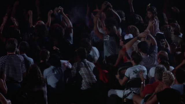 PAN RIGHT ON YOUNG AUDIENCE IN EARLY 1980'S ATTIRE WATCHING ROCK CONCERT. SEVERAL MEMBERS OF THE CROWD WITH ARMS IN AIR, CLAPPING AND PUMPING THE AIR, DANCING AND STOMPING THEIR FEET TO THE MUSIC. PAN BACK LEFT.