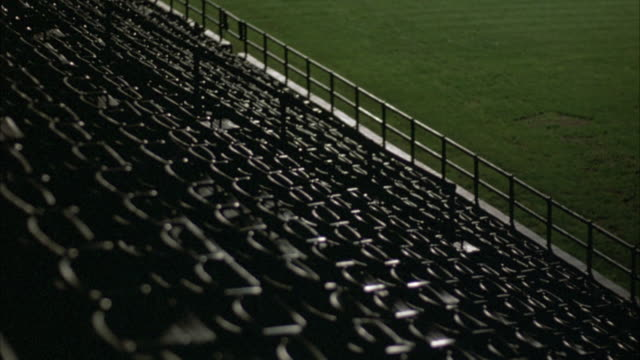 high angle down of bleacher seats in baseball stadium. pov from higher row of bleachers. see railing separating field from bleachers. shot slowly brightens different parts of bleachers and field. - anno 1939 video stock e b–roll