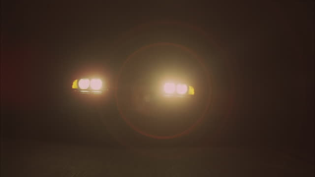 CLOSE ANGLE OF BMW 528I FROM AHEAD, DRIVING ON HIGHWAY ROAD. CAMERA STARTS WITH CLOSE ANGLE OF HEADLIGHTS AND CALIFORNIA LICENSE PLATE THEN PULLS BACK. CAR PULLS OVER TO SHOULDER OF ROAD. COULD BE RURAL AREA.