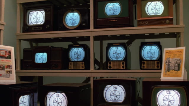 MEDIUM ANGLE ZOOM IN OF ANTIQUE OR VINTAGE TELEVISIONS ON THREE LEVELS OF SHELVES. SEE MANUALS ON BOOKLETS ON SIDES. MOST LIKELY IN STORE OR WAREHOUSE.