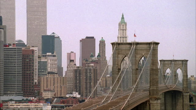 medium angle of brooklyn bridge. pans down and left to see hudson river and roads. world trade center twin towers. - brooklyn bridge stock videos and b-roll footage