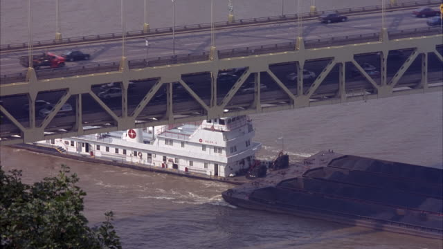HIGH ANGLE DOWN OF ALLEGHENY RIVER WITH BRIDGE ON TOP. SEE LARGE BARGE SLOWLY MOVING TO RIGHT UNDER BRIDGE. SOME TRAFFIC ON BRIDGE. FERRY IS ATTACHED TO BARGE PUSHING IT TO RIGHT.