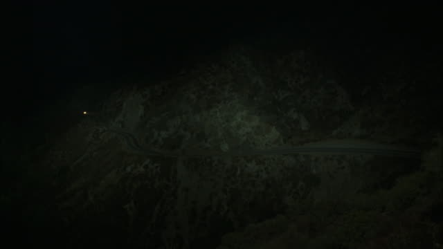 wide angle of compact car driving up winding two-lane mountain highway. headlights are on. rocks and desert brush along road. - compact car stock videos and b-roll footage