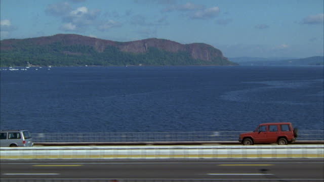 tracking shot of red suv driving on tappan zee bridge over hudson river. bridge links cities of tarrytown and nyack, visible on left. highways. hills with bluffs, cliffs in background. - sports utility vehicle stock videos and b-roll footage
