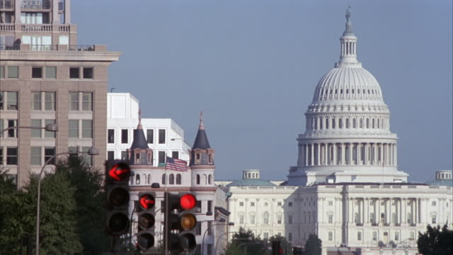 MEDIUM ANGLE OF CAPITOL BUILDING AT RIGHT AND OFFICE BUILDING AT LEFT. SEE STREET LAMPS AND SIGNALS IN FOREGROUND.