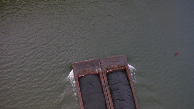 AERIAL OF TUGBOAT PUSHING COAL BARGE ON RIVER UNDERNEATH BRIDGE. CIRCLES TO RIGHT TO ROTATE AROUND BARGE.