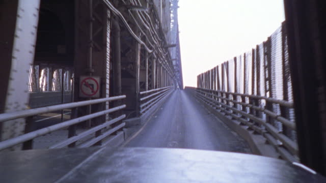 hand held driving pov of a car driving across the east river on the manhattan bridge.  the camera pans back to show the new york city skyline and back to brooklyn and a sign for silvercup studios. - manhattan stock videos & royalty-free footage