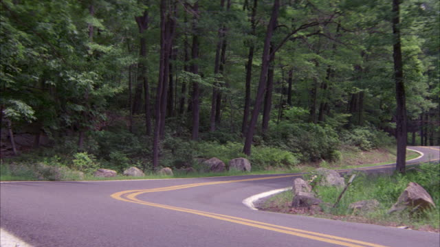 medium angle of curvy or winding country road with rocks and trees on the sides. see green car, possibly cadillac or oldsmobile, come from around the corner in the distance and speed around the curves and exit the screen right. - cadillac stock-videos und b-roll-filmmaterial