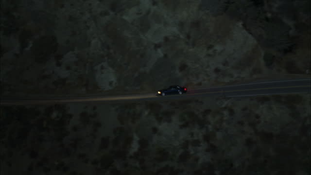wide angle of compact car driving down winding two-lane mountain highway. headlights are on. rocks and desert brush along road. - compact car stock videos and b-roll footage