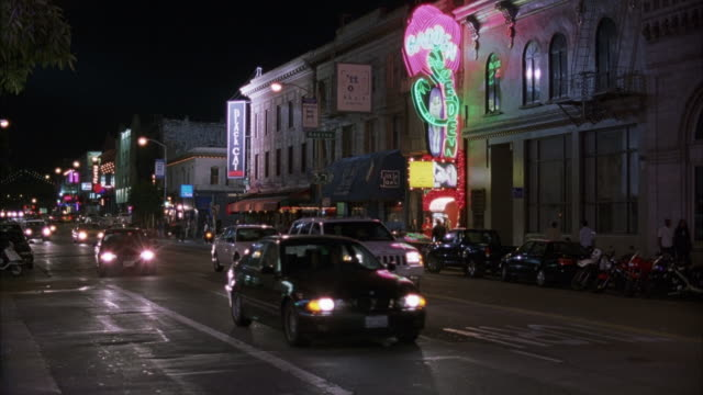 PAN L-R. DOWN BROADWAY STREET IN NORTH BEACH. TRAFFIC APPROACHING FROM BG.  SEE GARDEN OF EDEN NEON SIGN ACROSS STREET OUTSIDE STRIP CLUB.  NIGHTCLUBS.
