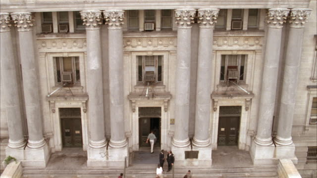 high angle down of entrance to courthouse or government building. see four pairs of stone corinthian columns on sides of three entrance doors. see people walk into building. - korinthisch stock-videos und b-roll-filmmaterial