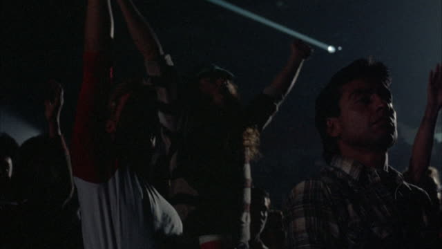 CLOSE UP. TWO SILHOUETTED YOUNG MALE ROCK CONCERT AUDIENCE MEMBERS DRESSED IN EARLY 1980'S ATTIRE, CHEERING WITH ARMS RAISED PUMPING THE AIR.
