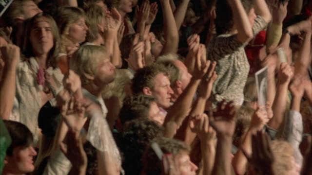 clip is a close up pan right to left  of a rock concert audience (young and dressed in early 1980's attire) crowd is shown with arms raised, clapping and pumping the air. - 拍手喝采点の映像素材/bロール