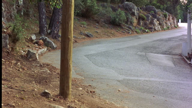WIDE ANGLE OF CITROEN DS 21 CAR BEING CHASED BY 1985 BMW 520I SEDAN ON WINDING COUNTRY OR MOUNTAIN ROAD. CARS SWERVE ONTO DIRT ROAD