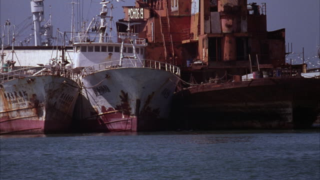 WIDE ANGLE OF TWO LARGE OLD RUSTY SHIPS OR FISHING BOATS NEXT TO A RUSTY BARGE DOCKED IN AN OCEAN HARBOR. SEE TWO DINGHIES DRIVE BY IN FRONT.
