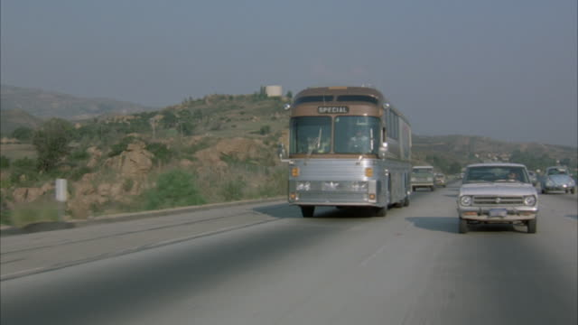 wide angle tracking shot of passenger bus traveling down desert highway, several other cars, of various makes and sizes from early 1980's travel in same direction as bus, toward shot. - 1980 stock videos and b-roll footage