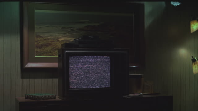 MEDIUM ANGLE OF 1970S OR 1980S TELEVISION IN LOWER CLASS MOTEL ROOM. TELEVISION IS TURNED ON WITH STATIC ON SCREEN. VCR ON TOP OF TELEVISION. TELEVISION SITS ON DRAWERS. LIGHTS AND PAINTING OF OCEAN SCENE IN BG. GENERAL DECOR IS 1970S AND LOWER CLASS.
