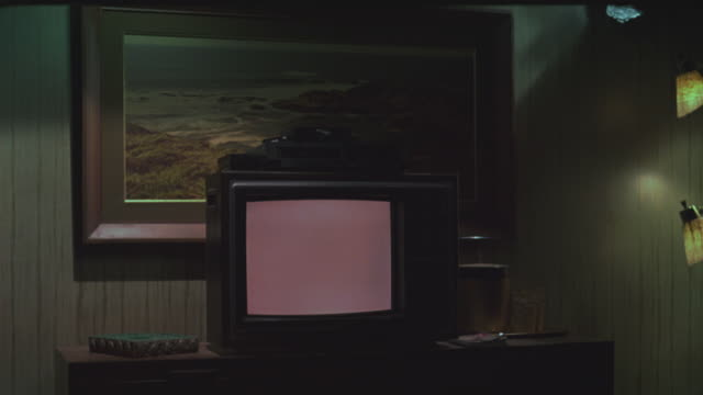 MEDIUM ANGLE OF 1970S OR 1980S TELEVISION IN LOWER CLASS MOTEL ROOM. TELEVISION IS TURNED ON WITH BLANK SCREEN. VCR ON TOP OF TELEVISION. TELEVISION SITS ON DRAWERS. LIGHTS AND PAINTING OF OCEAN SCENE IN BG. GENERAL DECOR IS 1970S AND LOWER CLASS.